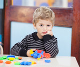 Fototapety Unhappy Boy With Blocks In Classroom