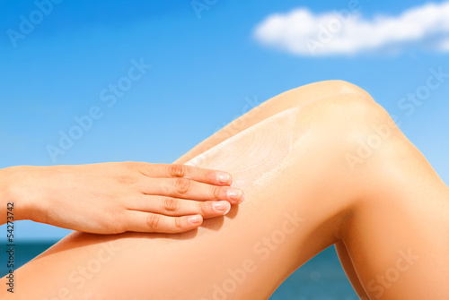Woman applying sunscreen on her skin