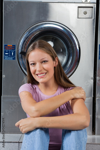 Beautiful Woman Sitting Against Washing Machine