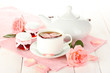 teapot and cup of tea with roses and jam on white wooden table