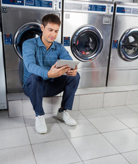 Man Using Digital Tablet While Sitting Against Washing Machines