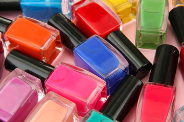 Group of bright nail polishes, on pink background