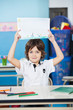 Boy Holding Drawing Paper At Desk In Kindergarten