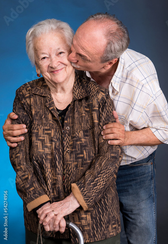A grown son kissing his aging mom