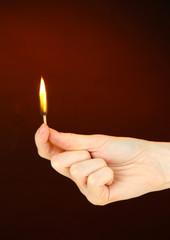 Burning match in female hand, on dark brown background