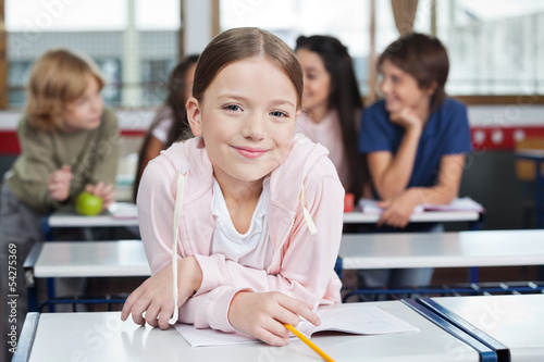 Schoolgirl Smiling While Leaning On Desk
