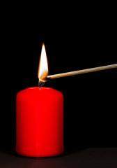Streichholz zündet Kerze an
