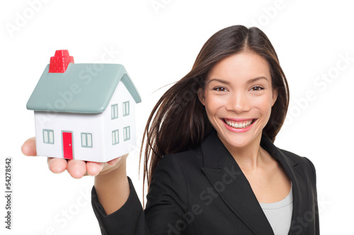 Real estate agent selling home holding mini house