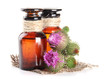 Medicine bottles with thistle flowers, isolated on white