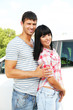 Portrait of happy beautiful couple standing near car
