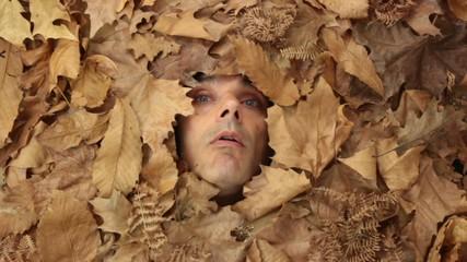 sneezing man under falling leaves, autumnal concept