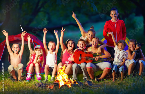 happy kids singing songs around camp fire - 54283377