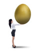 Attractive businesswoman holding big golden egg - isolated