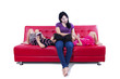 Beautiful mom and children on red sofa - isolated