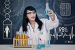 Beautiful scientist analysing solutions on blue
