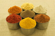 Spices in silver cooking pots, on hessian background