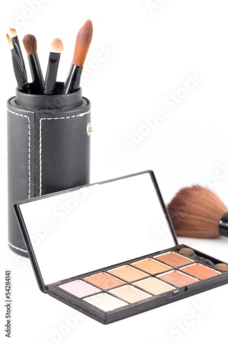 makeup brush and earth tone eyeshadow