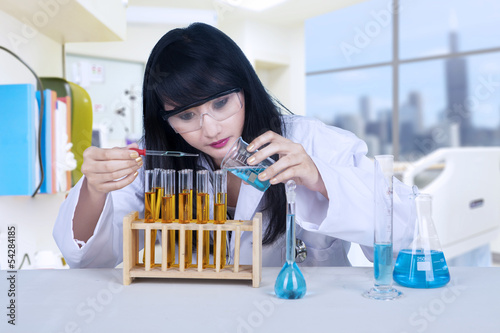 Beautiful scientist pouring liquid at lab