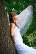 pensive bride in white dress standing and holding veil
