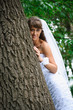smile bride in white dress standing near tree