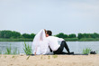 loving wedding couple sitting and kissing near water
