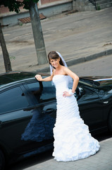happy bride in white dress standing near wedding car