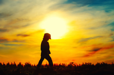 Young silhouetted child at sunset sky