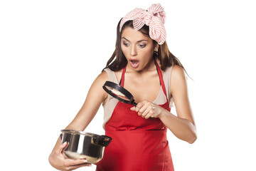 shocked housewife looking through the lens of her pot with food