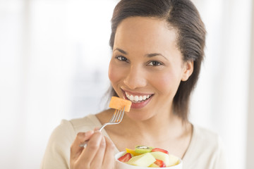Woman Eating Fresh Fruit Salad At Home