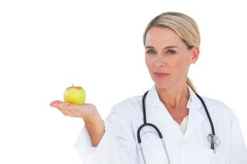 Smiling doctor holding apple and looking at camera