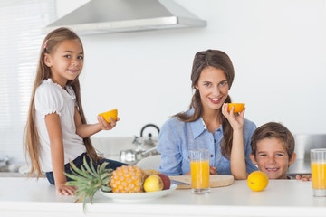 Siblings raising a half orange in the kitchen