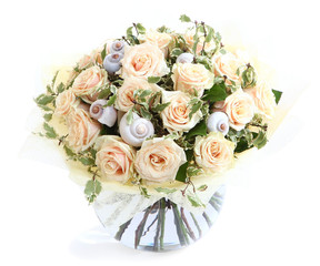 Flower arrangement with cream roses and shells, glass vase.