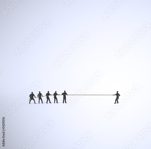 A tug of war between a group of people and a single man