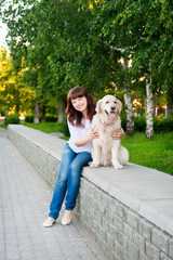 Young woman with a golden retriever in park