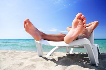 Young man sunbathe on beach bed at summer sea beach