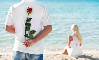 loving couple - man with rose waiting his woman on sea beach - r