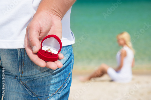 man making proposal with engagement ring to his woman on sea bea