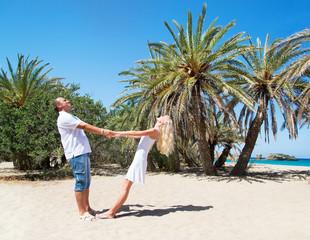 loving couple against tropical palm sea beach