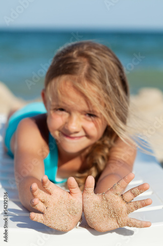 Happy little girl with sandy hands on the beach