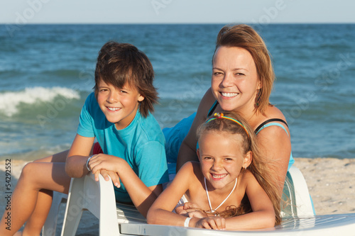 Happy woman and kids relaxing on a deck chair by the sea