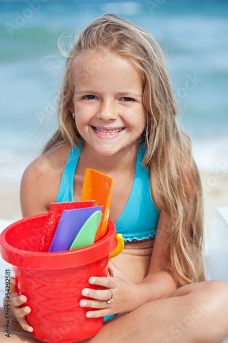 Little girl on the beach with small bucket and shovels for sand