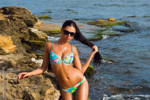Young girl in a swimsuit on the rocks near the sea