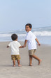 Two Young Boy Children Brothers Playing on Beach
