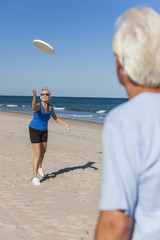 Healthy Senior Man Woman Couple Playing Beach Frisbee