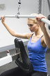 Woman Exercising On Pulley At Gym