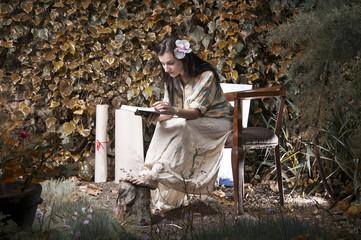 Beautiful girl reading a book in garden