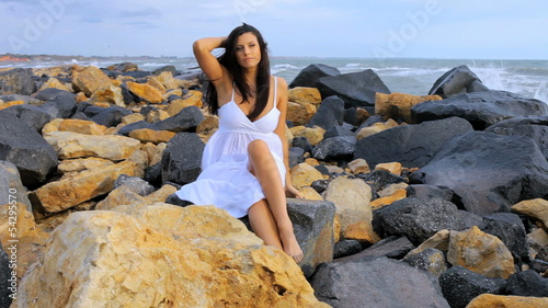 Beautiful female model posing on rocks