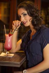 Attraktive brünette Frau trinkt Milchshake