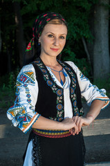 Portrait of young beautiful woman posing outside in Romanian tra