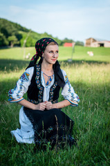 Young beautiful singer posing in traditional costume, romanian f
